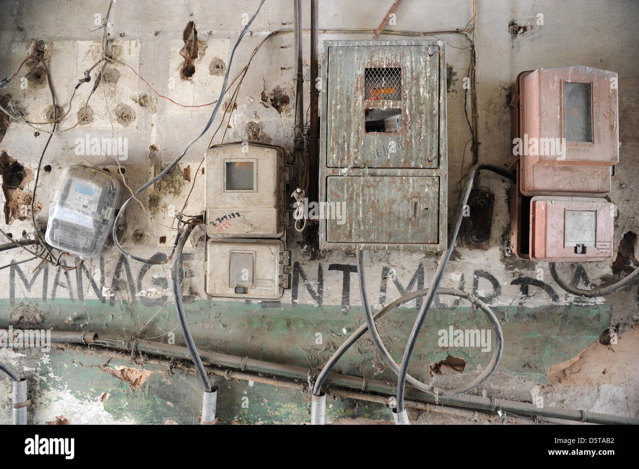 Old and decaying electric meters stand in the entrance to a house