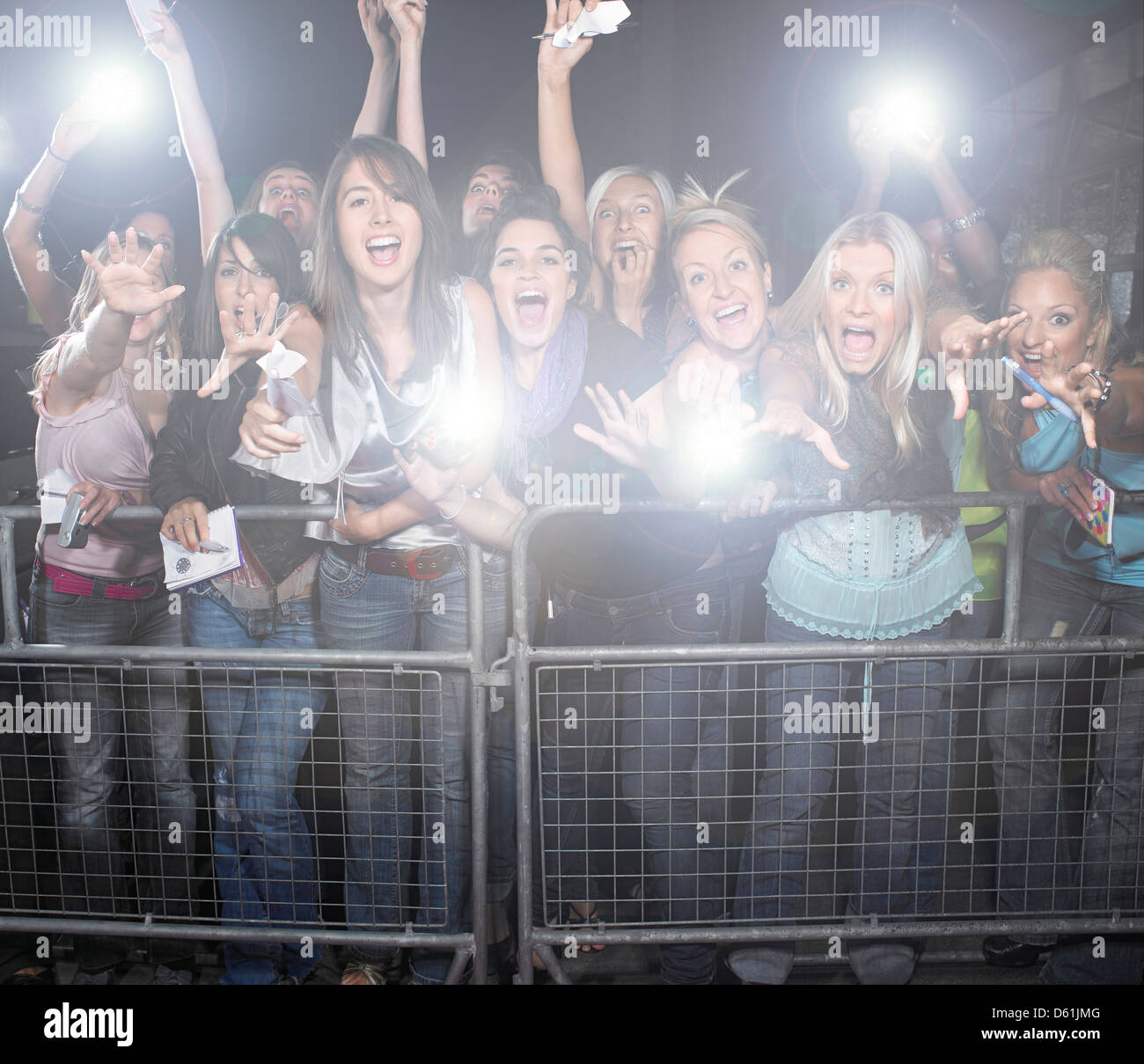 Fans taking pictures with cell phone behind barrier stock photo - Crowd Of Young Female Fans Screaming Cheering T Concert Stock Image