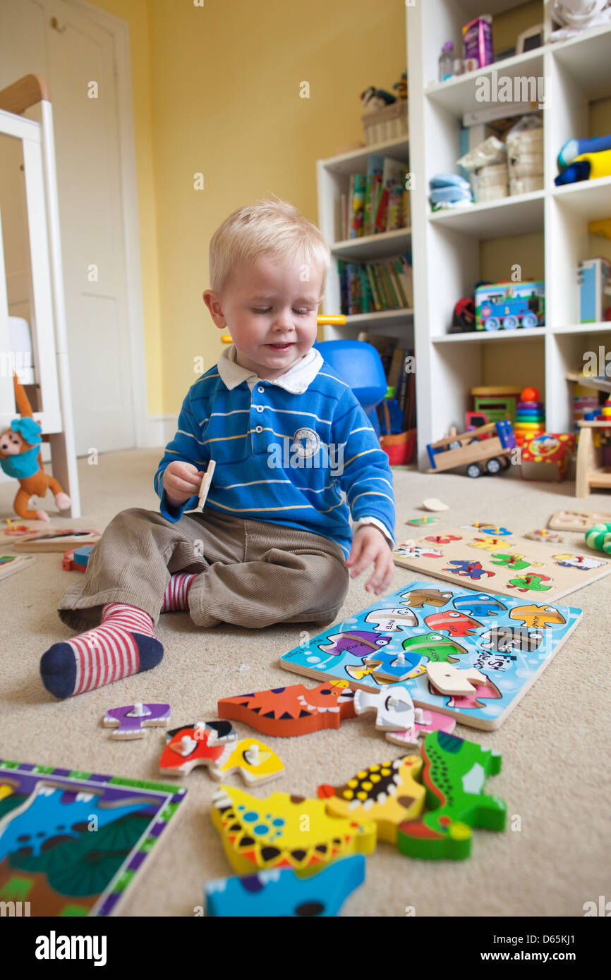 2 Year Old Boy Plays With Various Jigsaw Puzzles In His