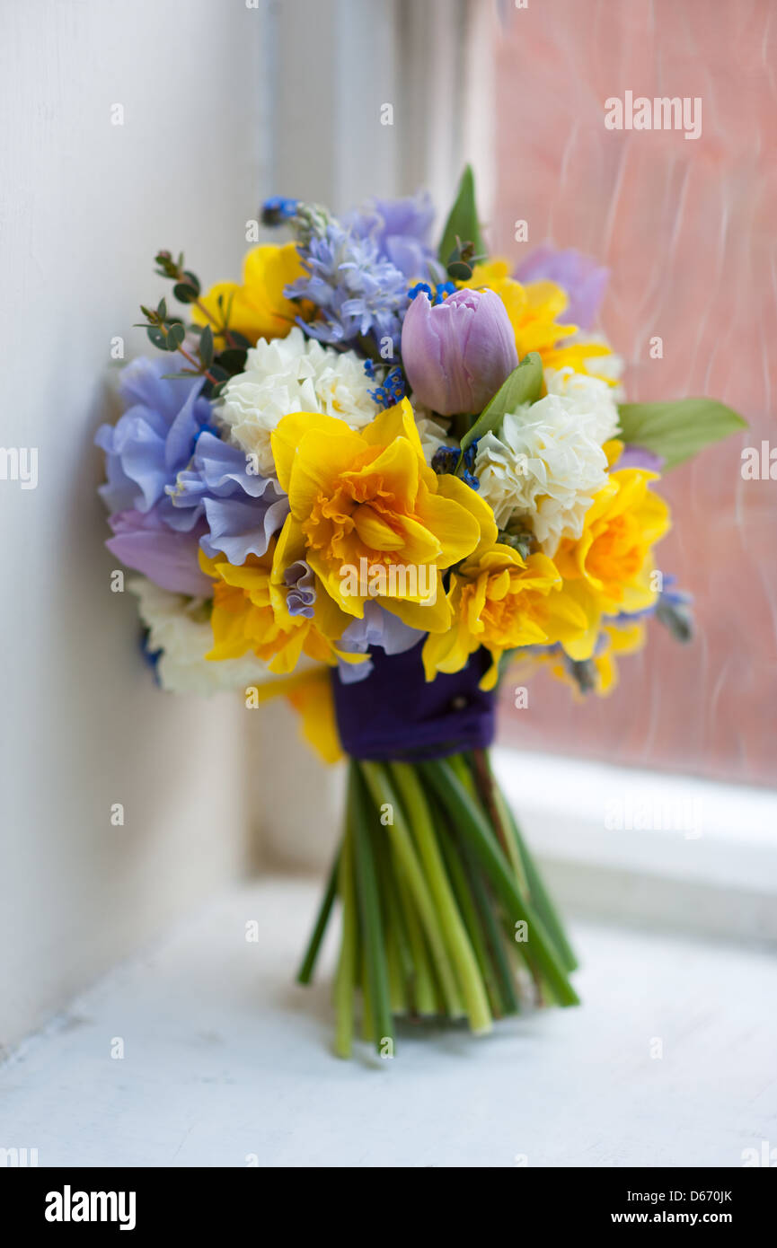 Wedding Bouquet Of Spring Flowers Including Daffodil Sweet Pea Tulip In Yellow Blue Pink And Purple By A Window