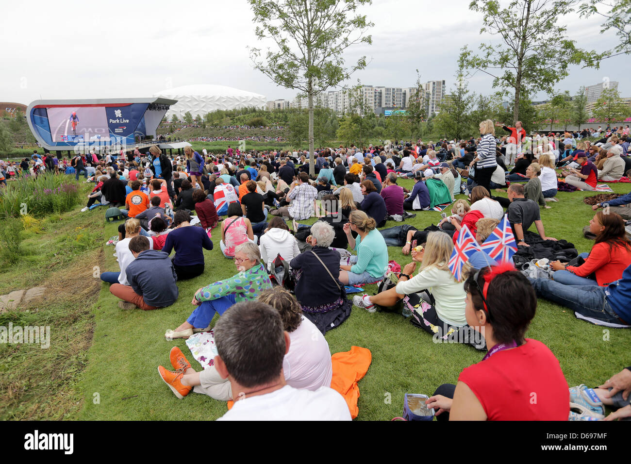 People Sit In The Olympic Park And Watch Cycling Event On A Huge TV Screen At London 2012 Games Great Britain 01 August