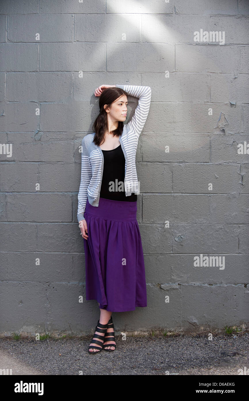Young Woman in Purple Skirt and Grey Sweater Leaning Against Wall ...