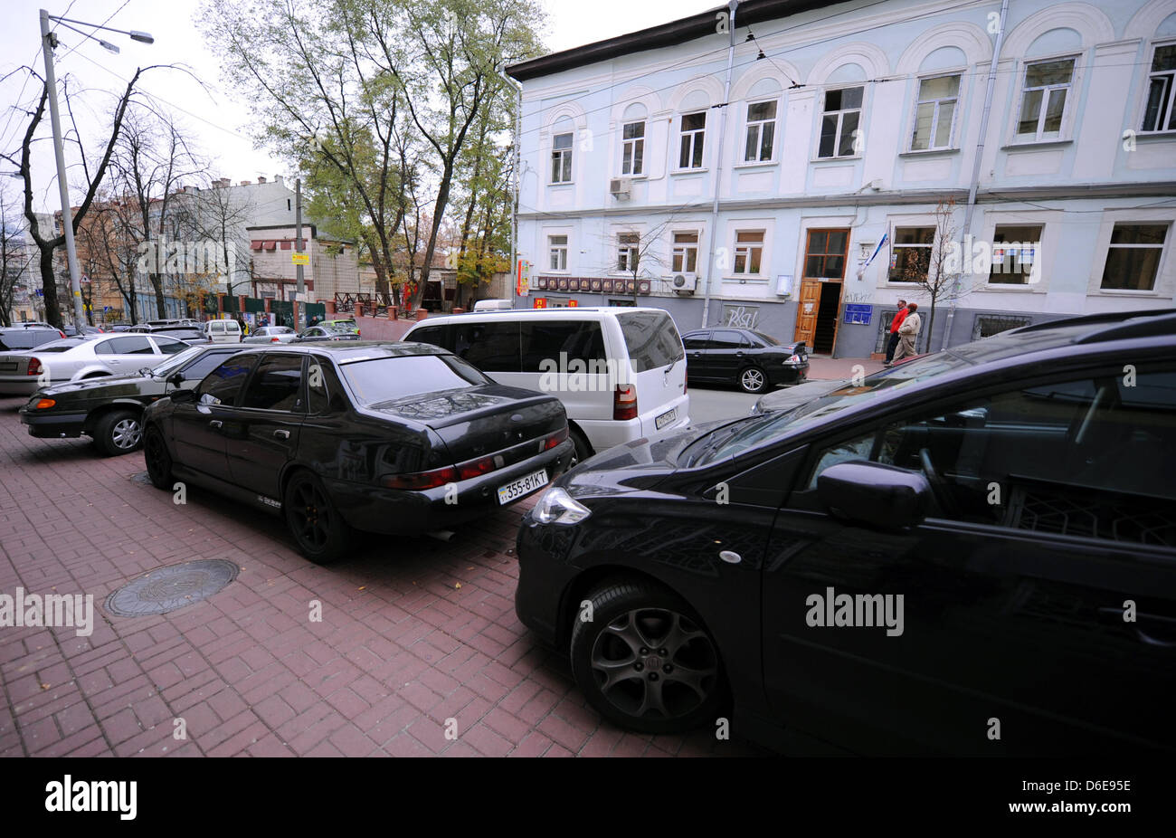 Cars park in two lanes on a street blocking the way for ...