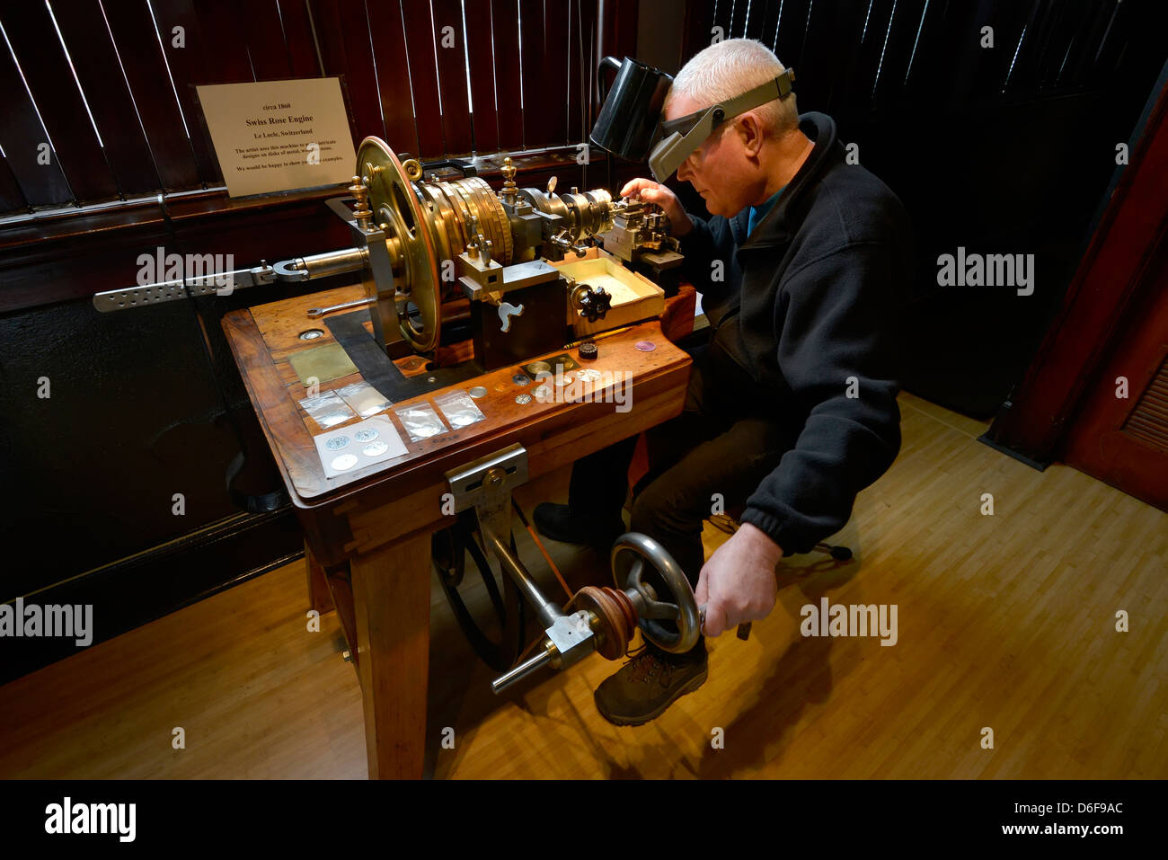 Jeweler engraving a piece of jewelry on an antique rose engine ...
