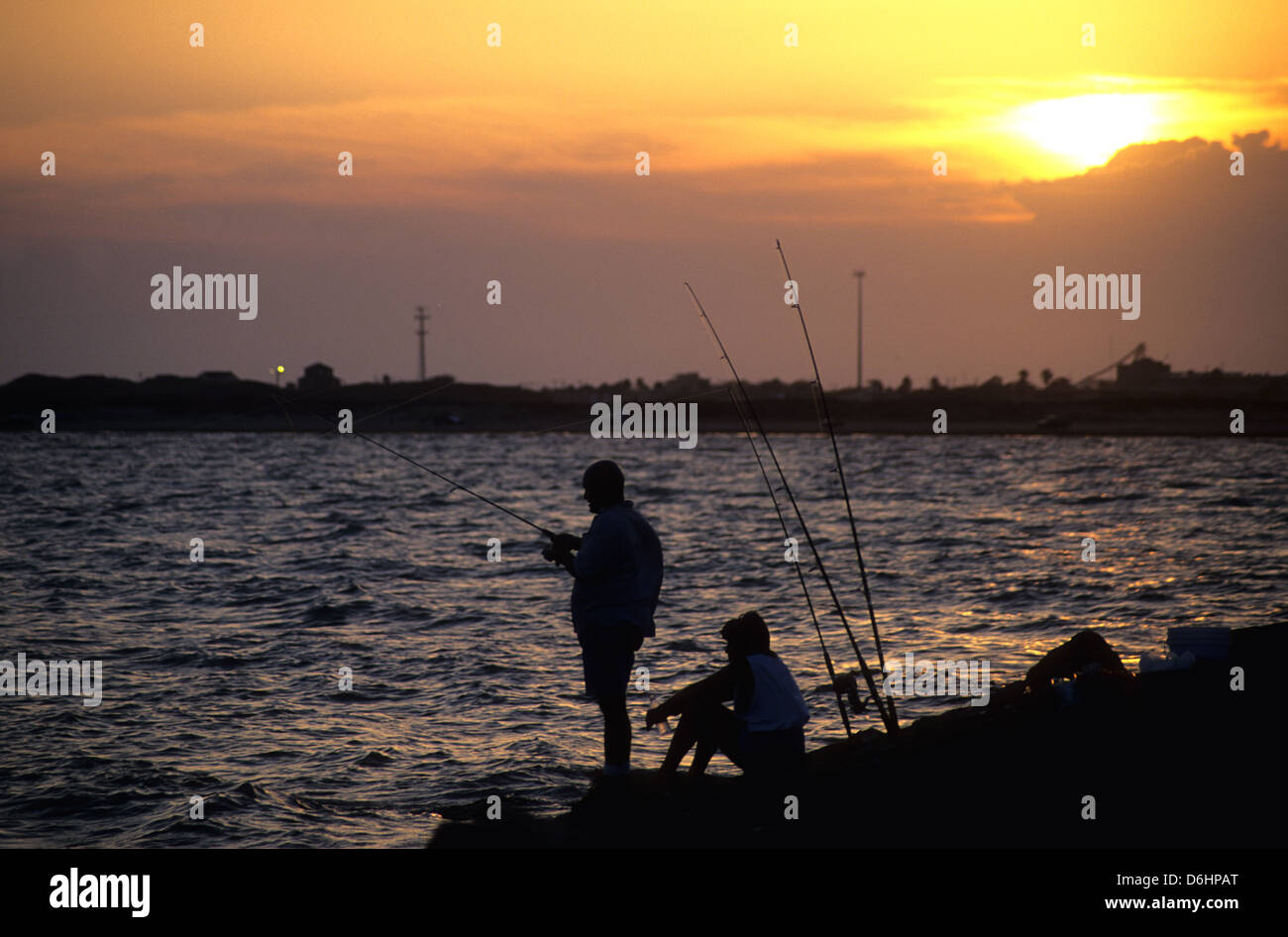 Two people fishing at sunset on the jetties at port for Port aransas jetty fishing report