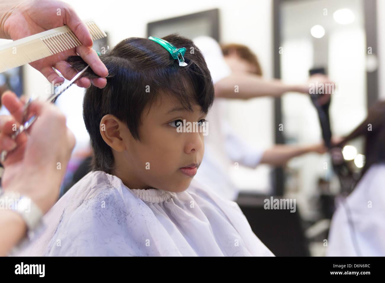 A Young Boy Getting Haircut In Hair Salon