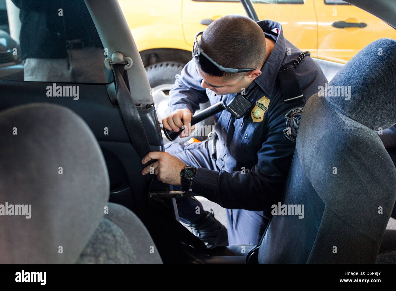 A US Customs And Border Patrol Officer Searches A Vehicle