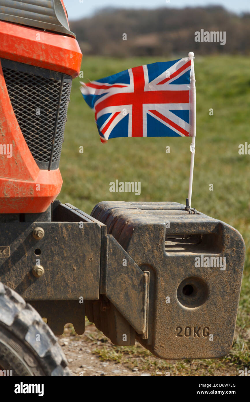 a union jack british flag on the front of a small red tractor