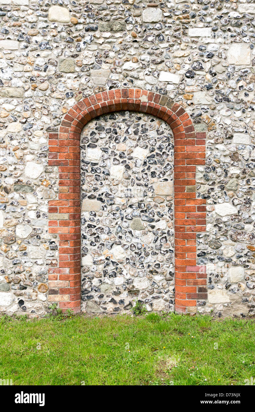 Blocked up doorway. Brick pillars and arch with flint and stone infill