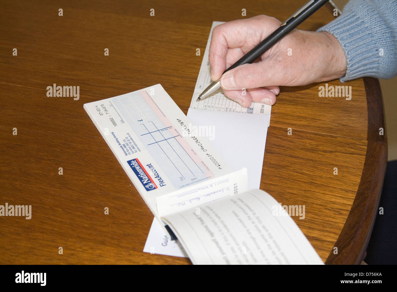 Uk Elderly Woman Sitting At Table Writing A Nationwide Cheque To Pay Into  Bank On Credit