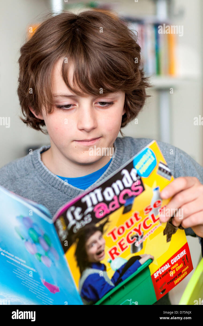 12 Year Old Boy Reading A News Magazine Stock Photo