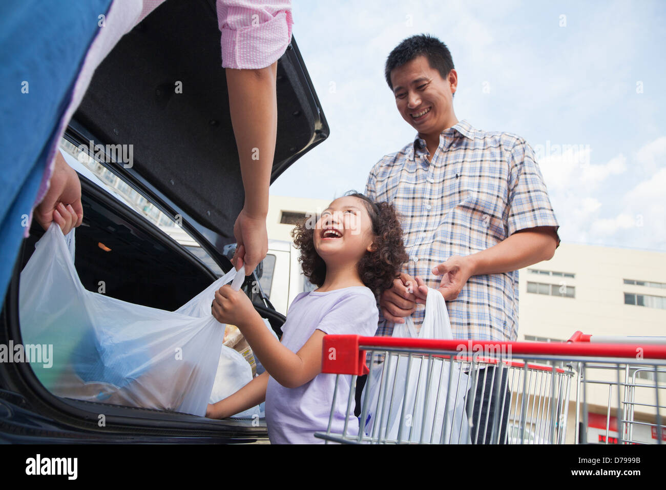 Family talking next to the car with shopping bags Stock Photo ...