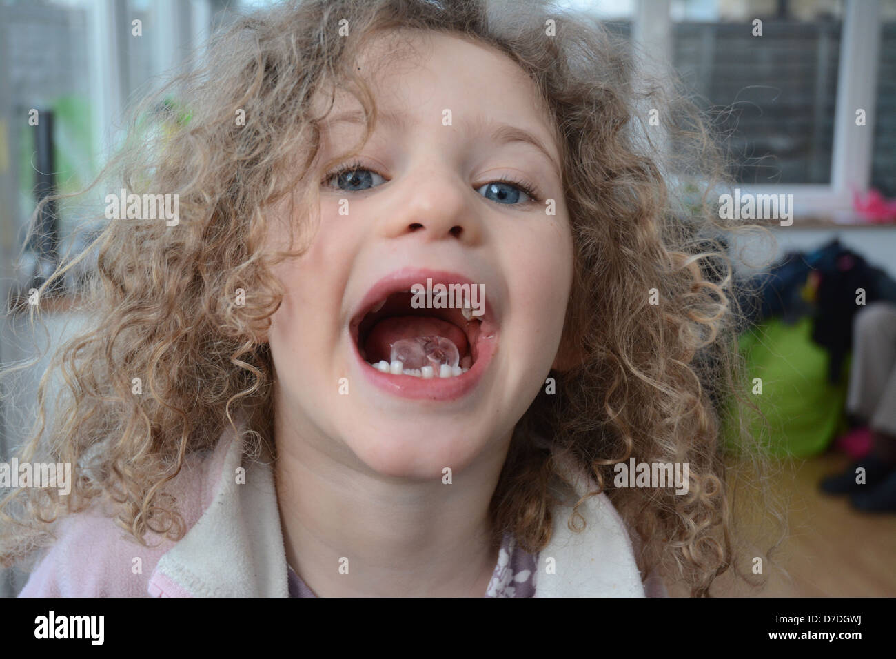 Five year old girl with curly hair and blue eyes showing