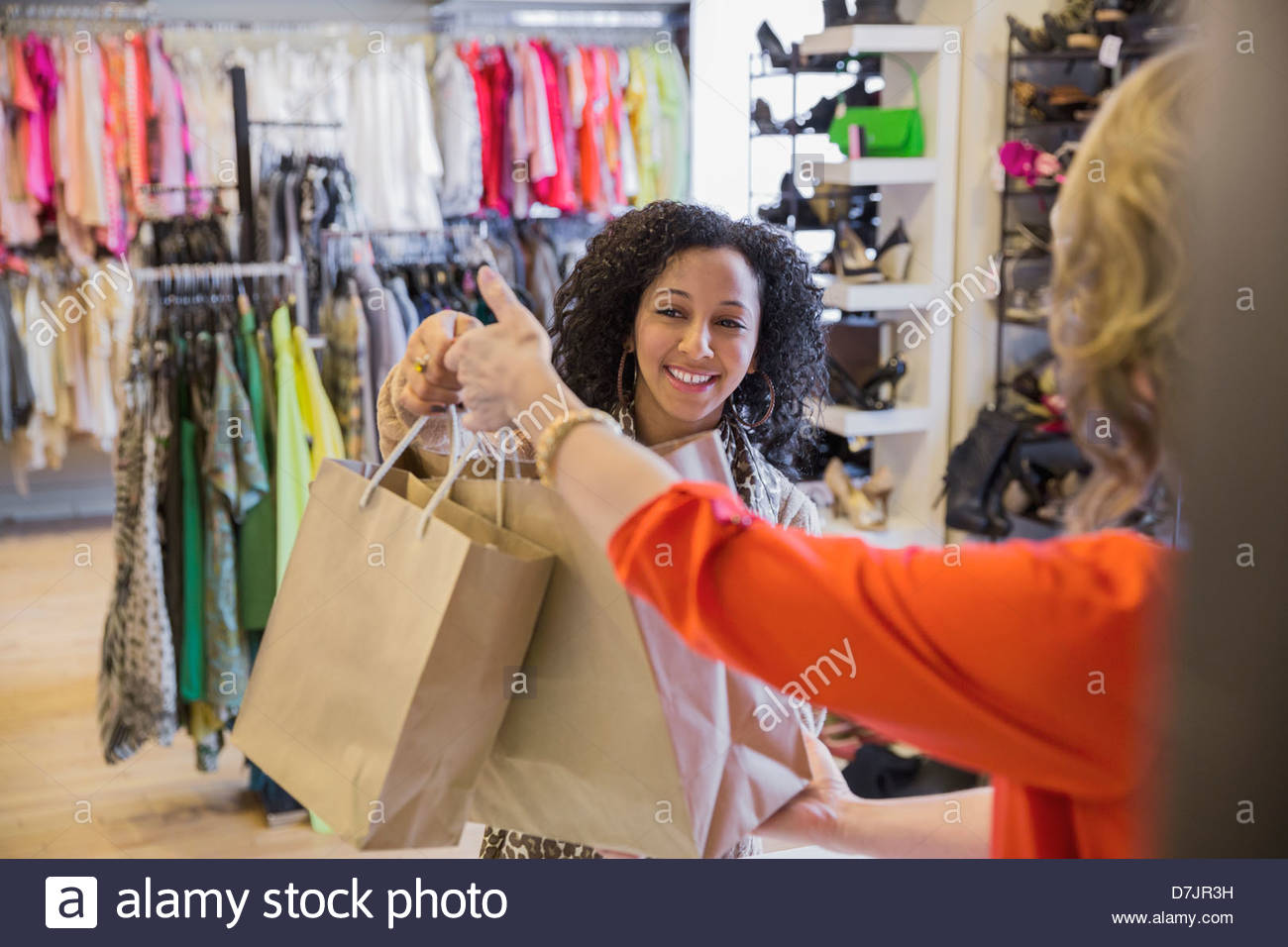 Female store owner passing shopping bags to customer at checkout ...