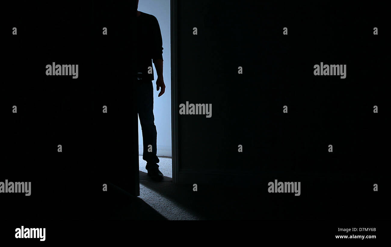 Silhouette of a man standing in an open door leading into a dark