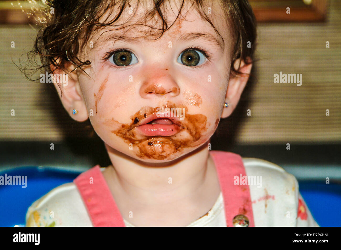 Baby with chocolate face enjoying birthday celebration after ...