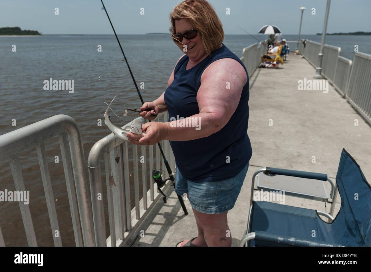 A woman fishing on the public pier at cedar key florida on for Cedar key fl fishing