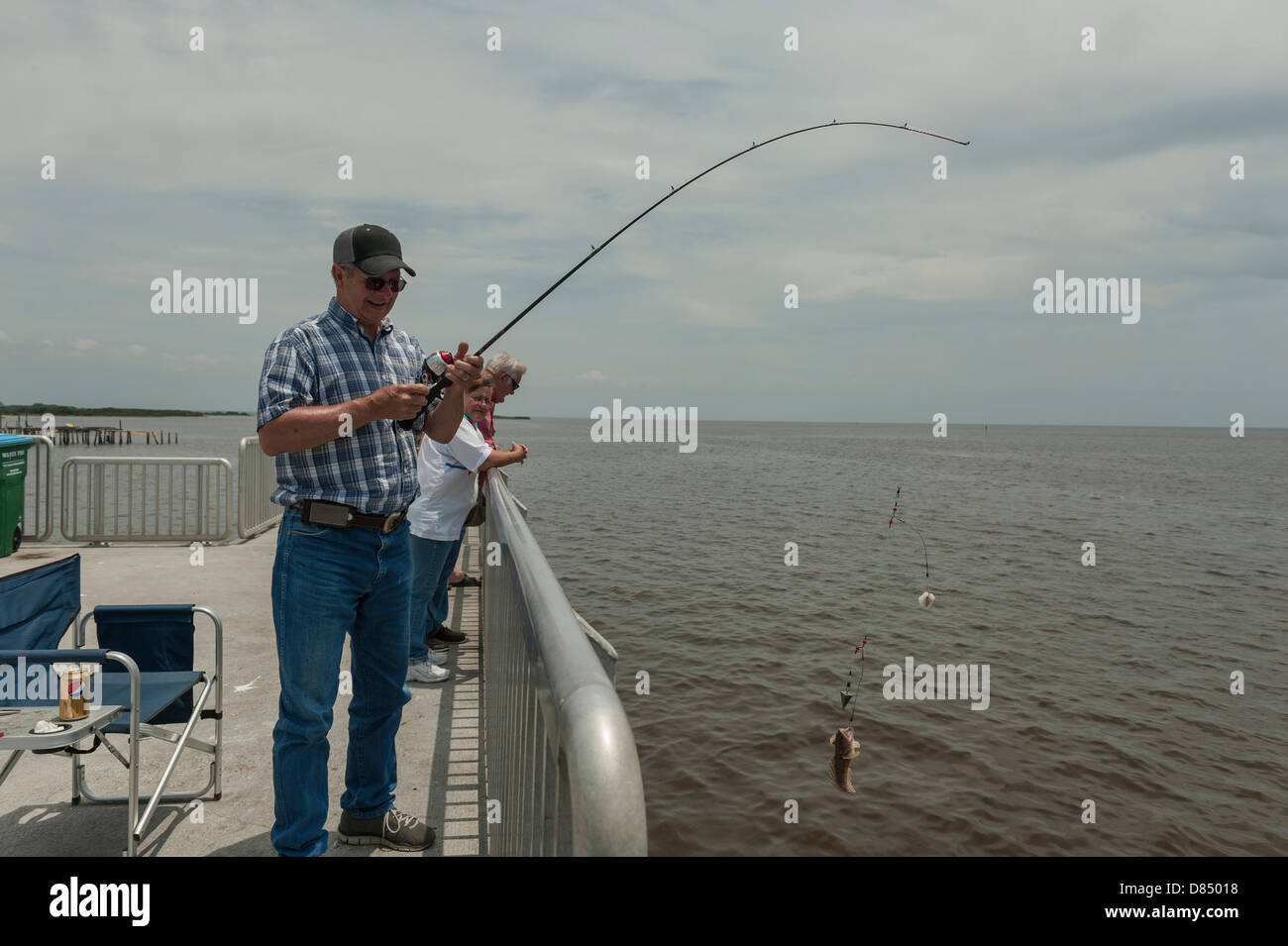 Man reeling in a fish on the public pier at cedar key for Cedar key fishing