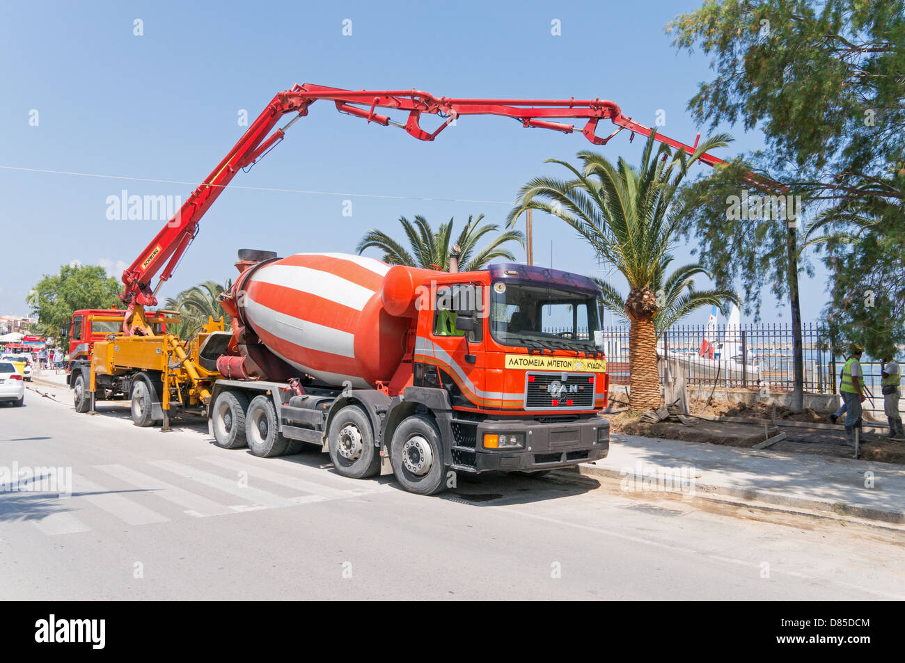 A concrete pump and cement mixer man truck working together in rethymno crete stock
