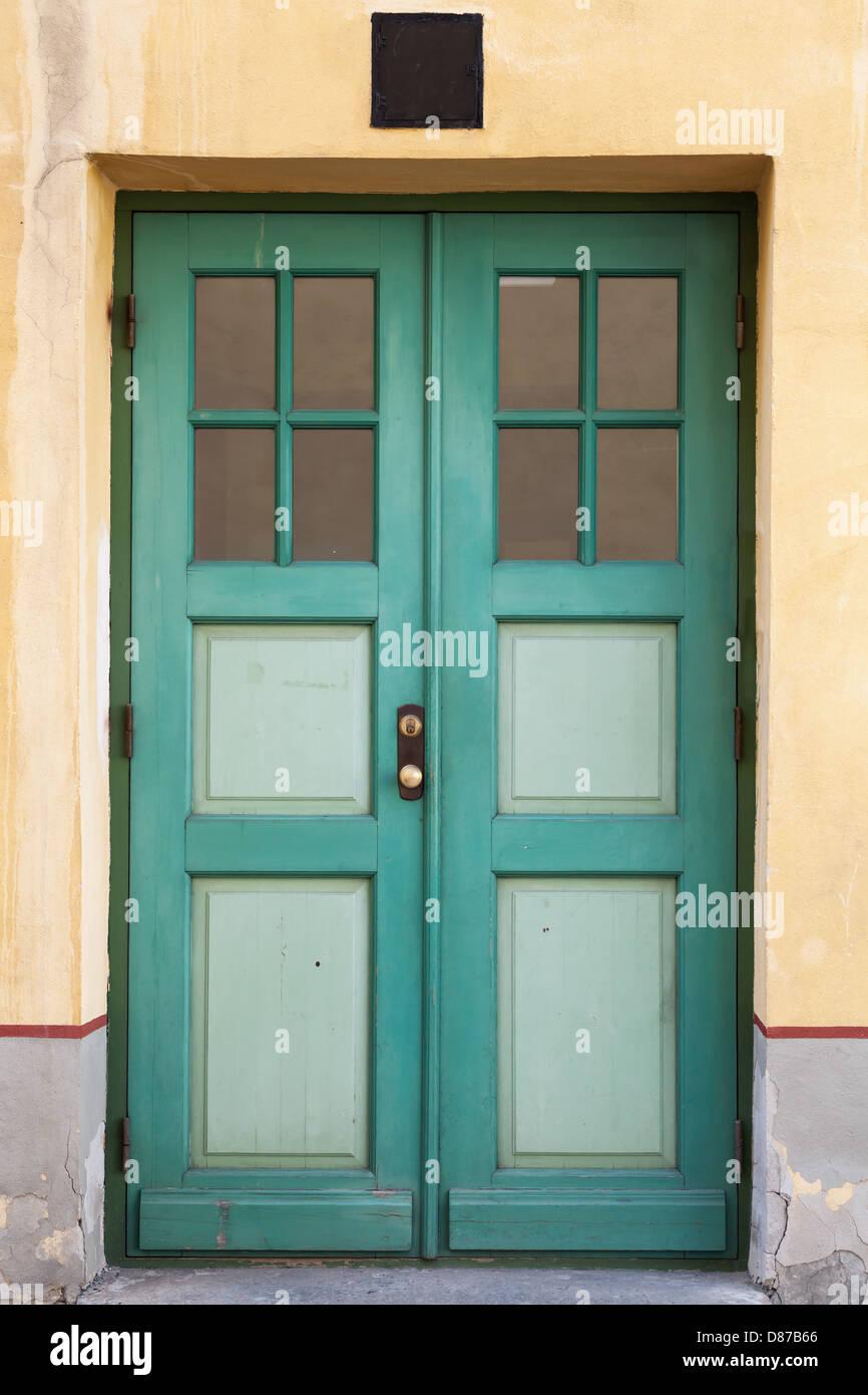 Green wooden door with windows in old building facade. Tallinn ...