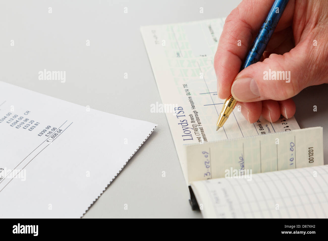 Elderly Woman Female Pensioner Writing A Lloyds Tsb Cheque To Pay A Large  Credit Card Bill England, Uk, Britain