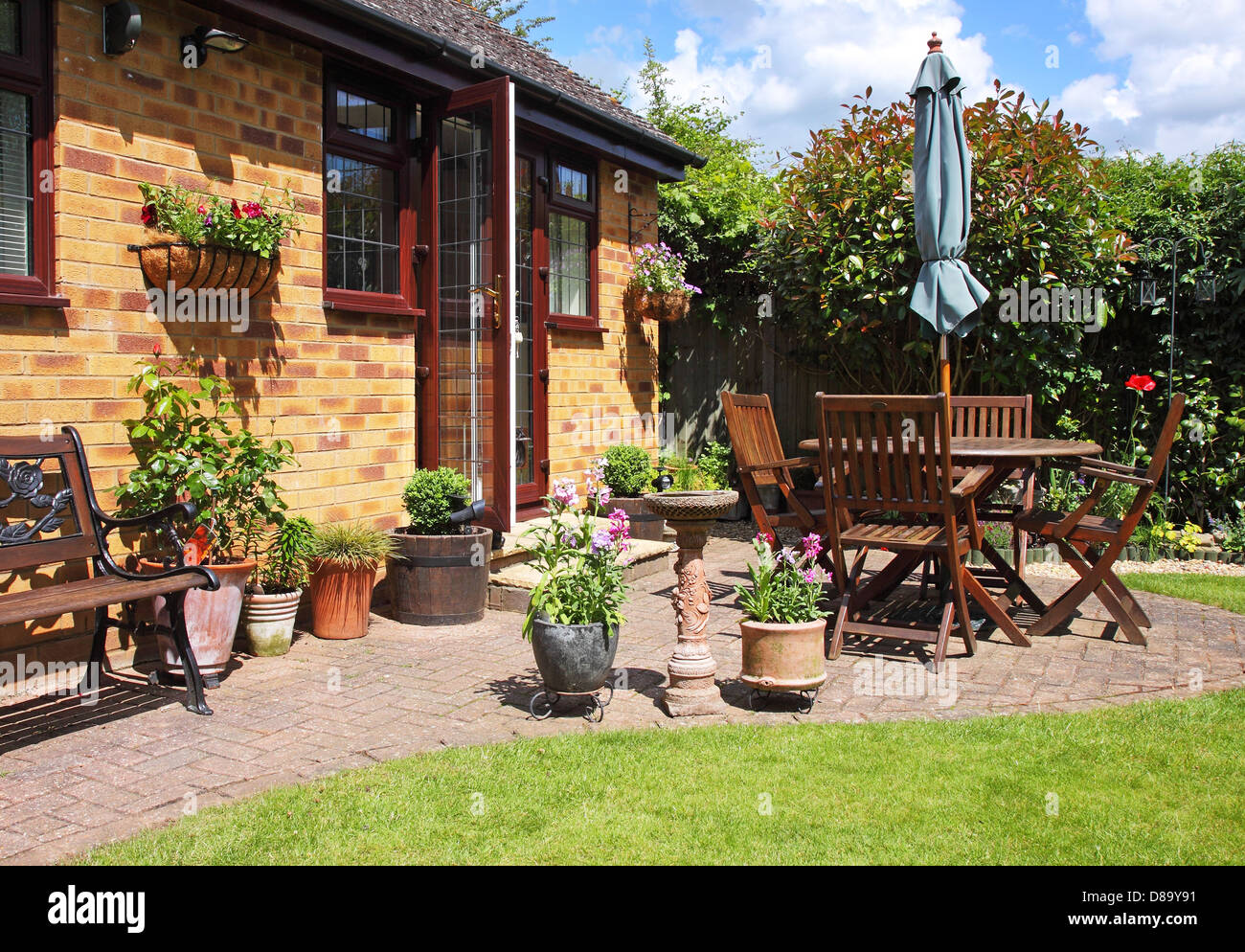 An English Back Garden Scene With Patio, Seating Area And Flowerpots    Stock Image