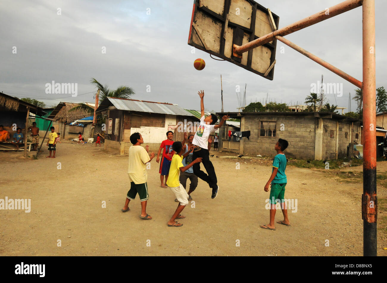 filipino men play basketball at the backyard near a mosque in the