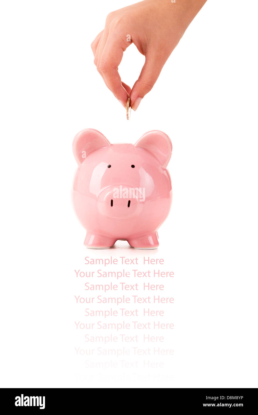 female hand putting a coin into piggy bank stock photo