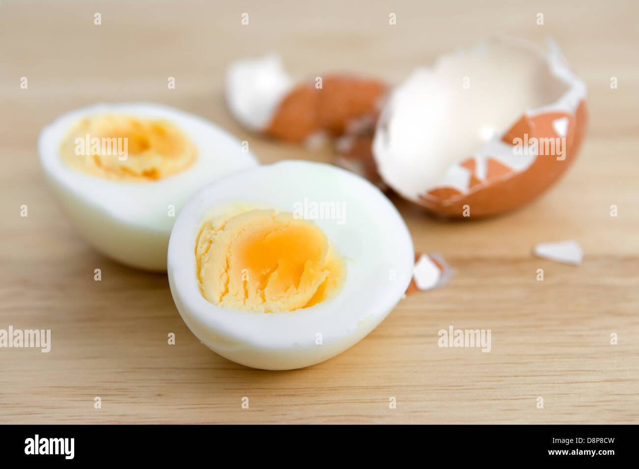 Hard boiled egg cut in half with egg shell on wooden chopping