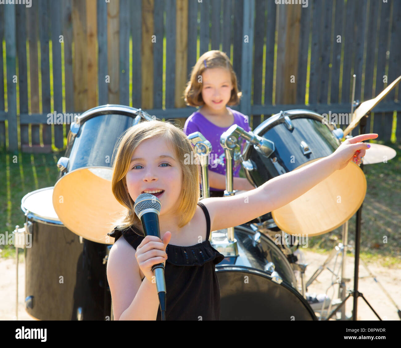 drummer blond kid playing drums in tha backyard stock photo