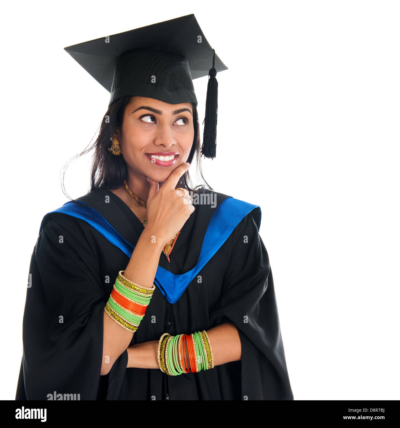 Happy Indian graduate student in graduation gown and cap thinking ...