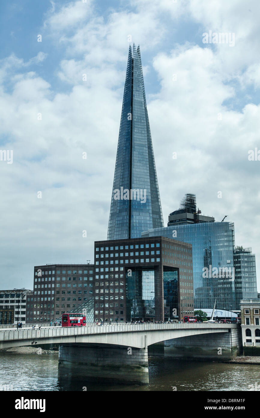 View of Red London bus going over London Bridge with the new Shard