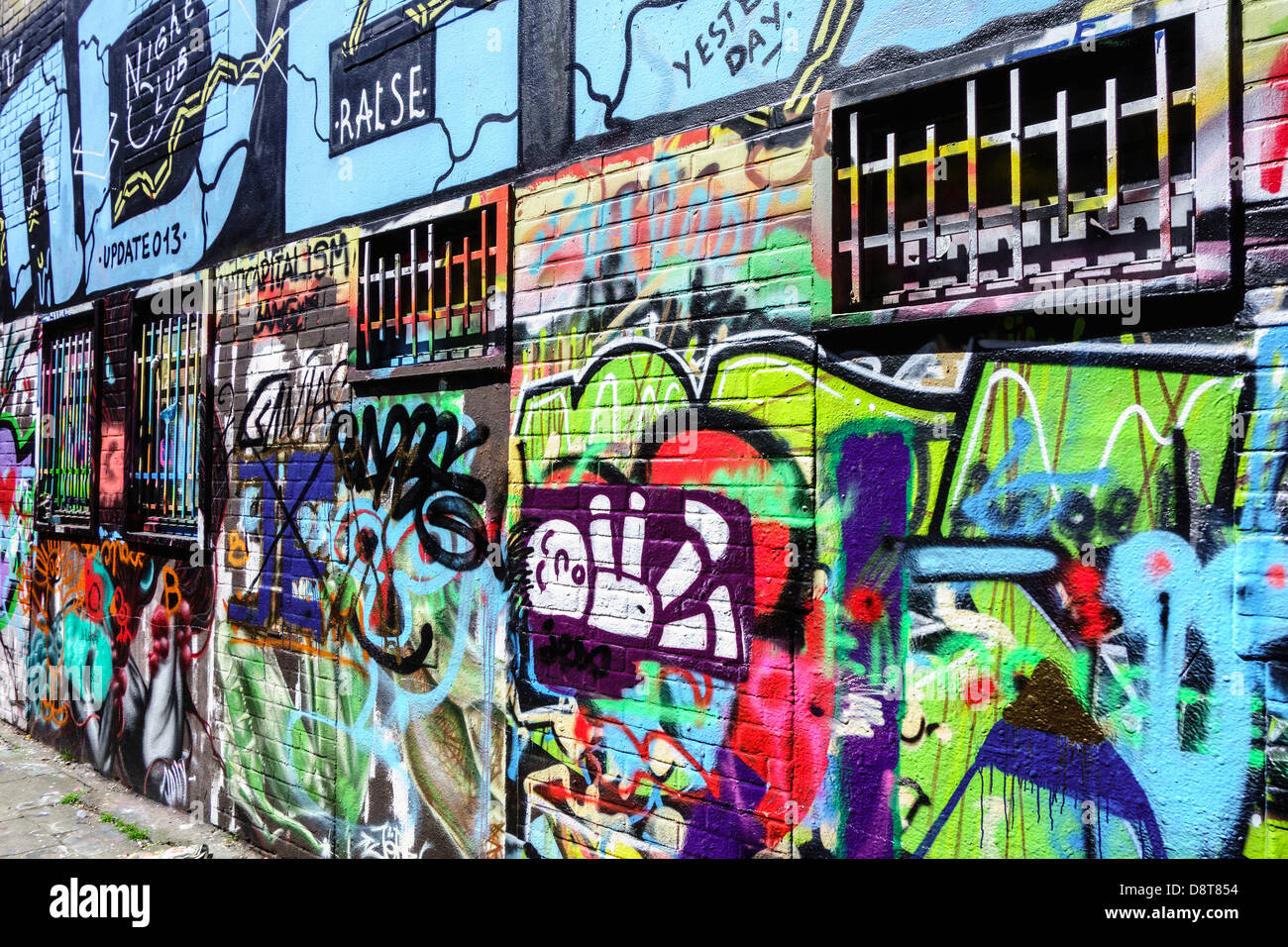 U2 graffiti wall - Colourful Graffiti In Alley On Wall Of Building In Town Stock Image