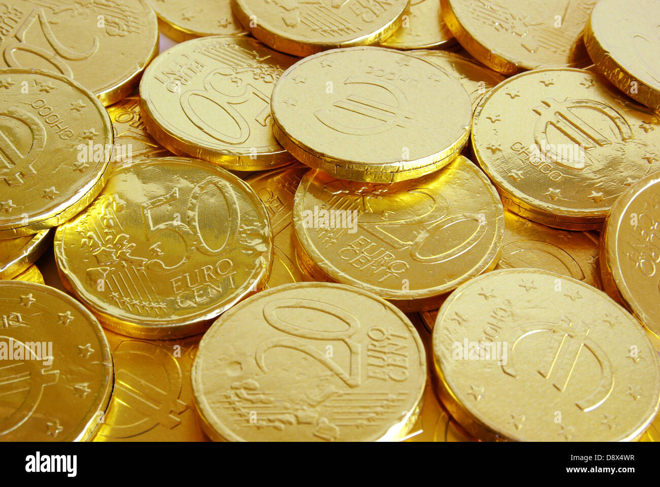 Pile of chocolate coins wrapped in shiny golden tinfoil Stock ...