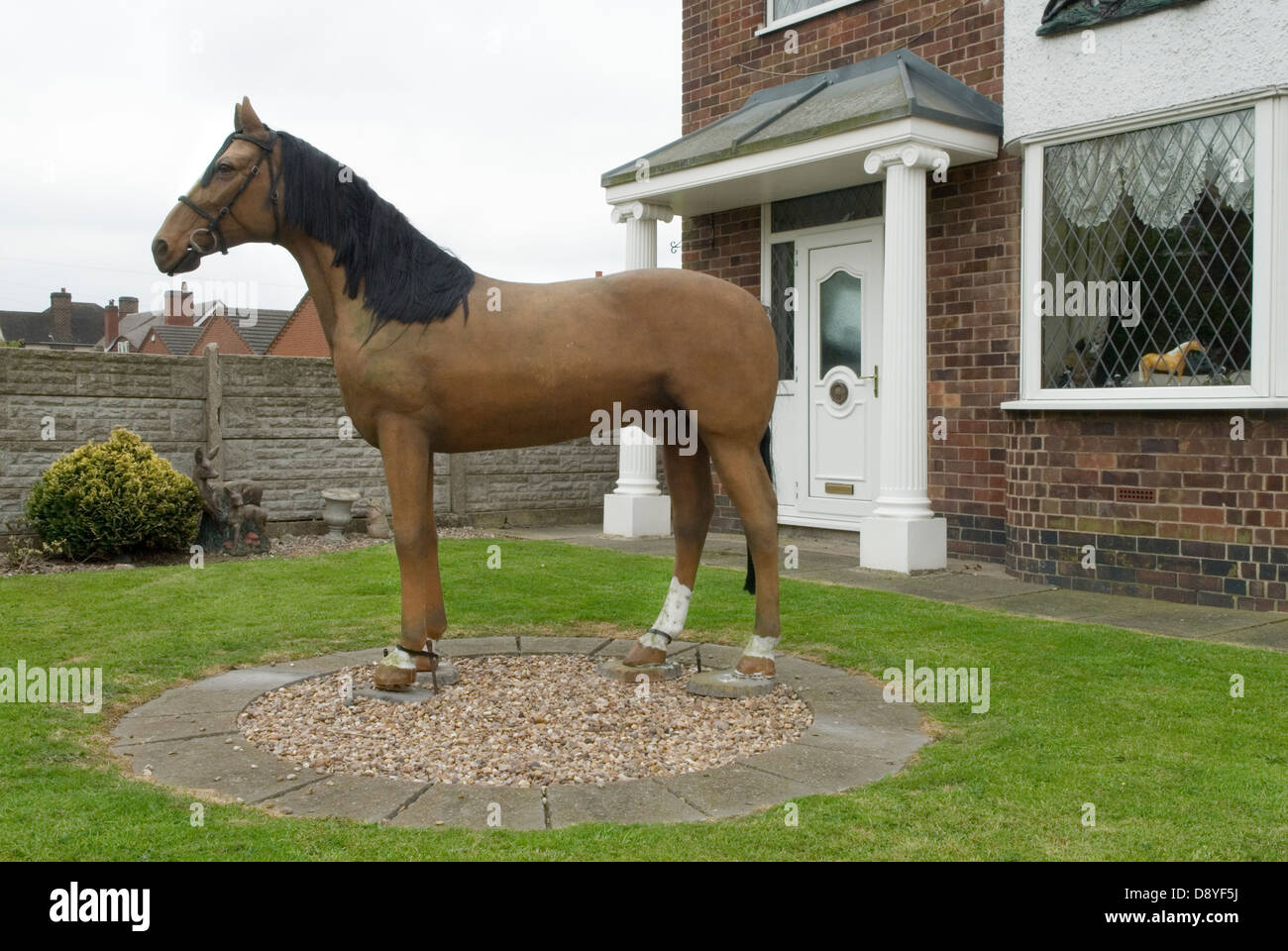 house decoration with fiber glass horse in front garden stock