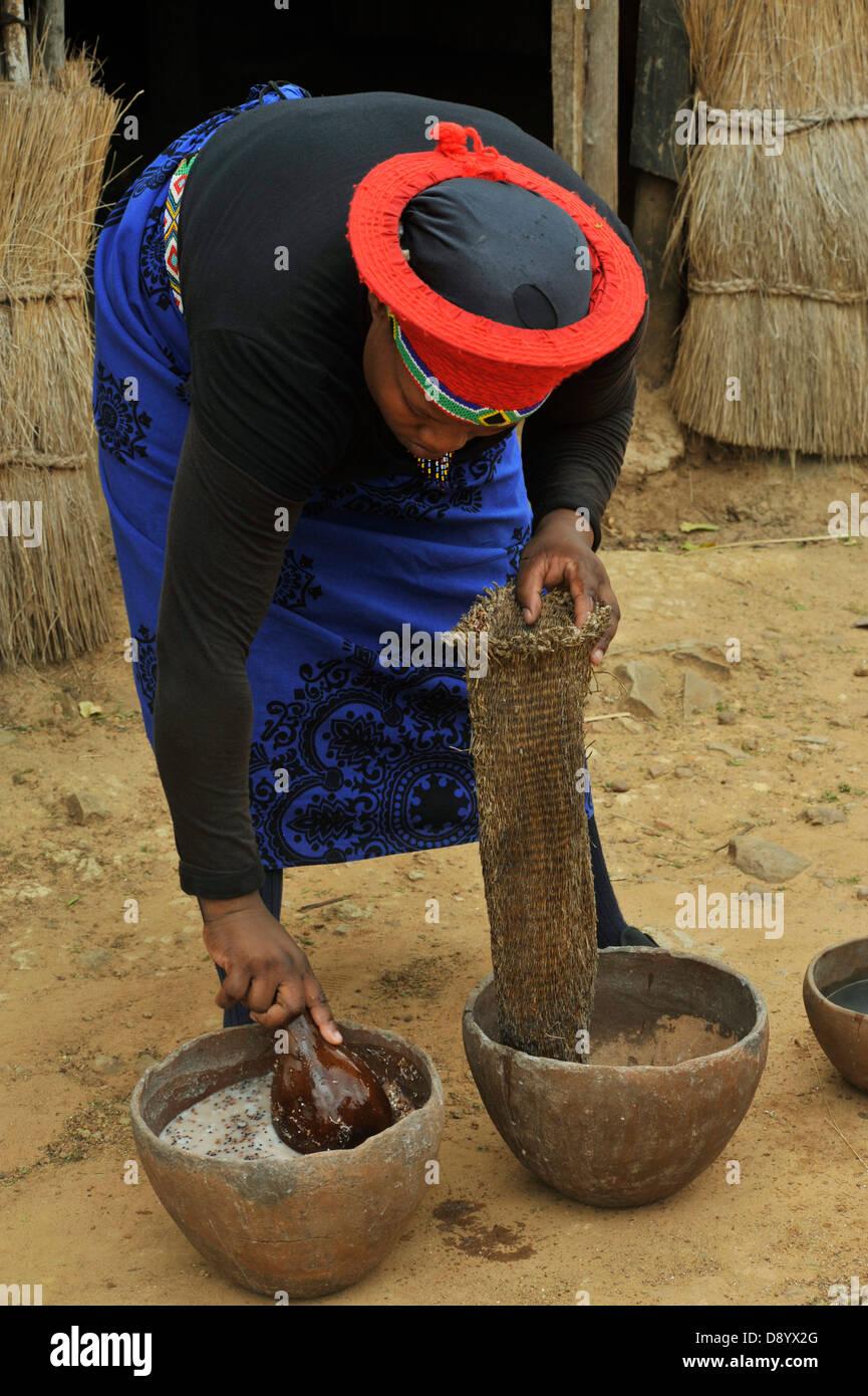 Zulu traditional dress in zulu kraal kwazulu natal - Zulu Wife In Traditional Dress Straining Sorghum Beer After Brewing Shakaland Kwazulu Natal South Africa