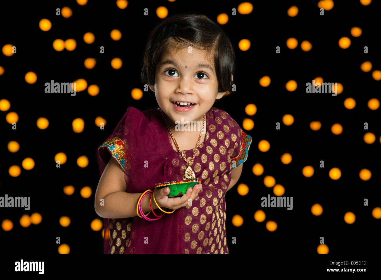 Girl holding an oil lamp and smiling in front of Diwali decoration ... for Girl Holding Lamp  83fiz