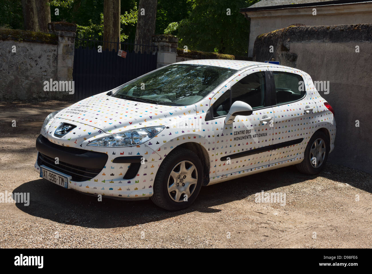 a parked peugeot 208 company car in the advertising livery of the