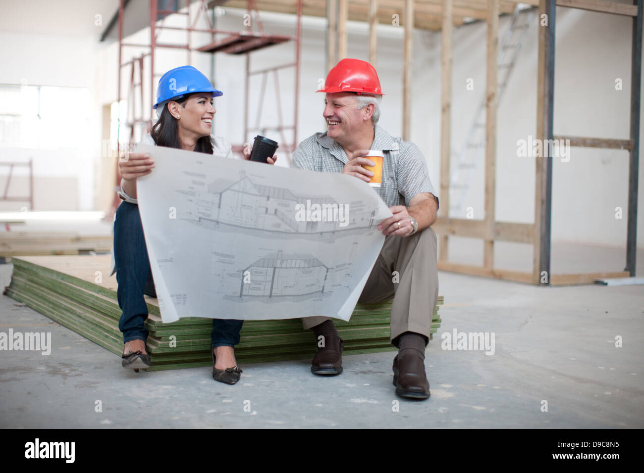 Male and female construction workers sitting down holding coffee male and female construction workers sitting down holding coffee and a blueprint malvernweather Images