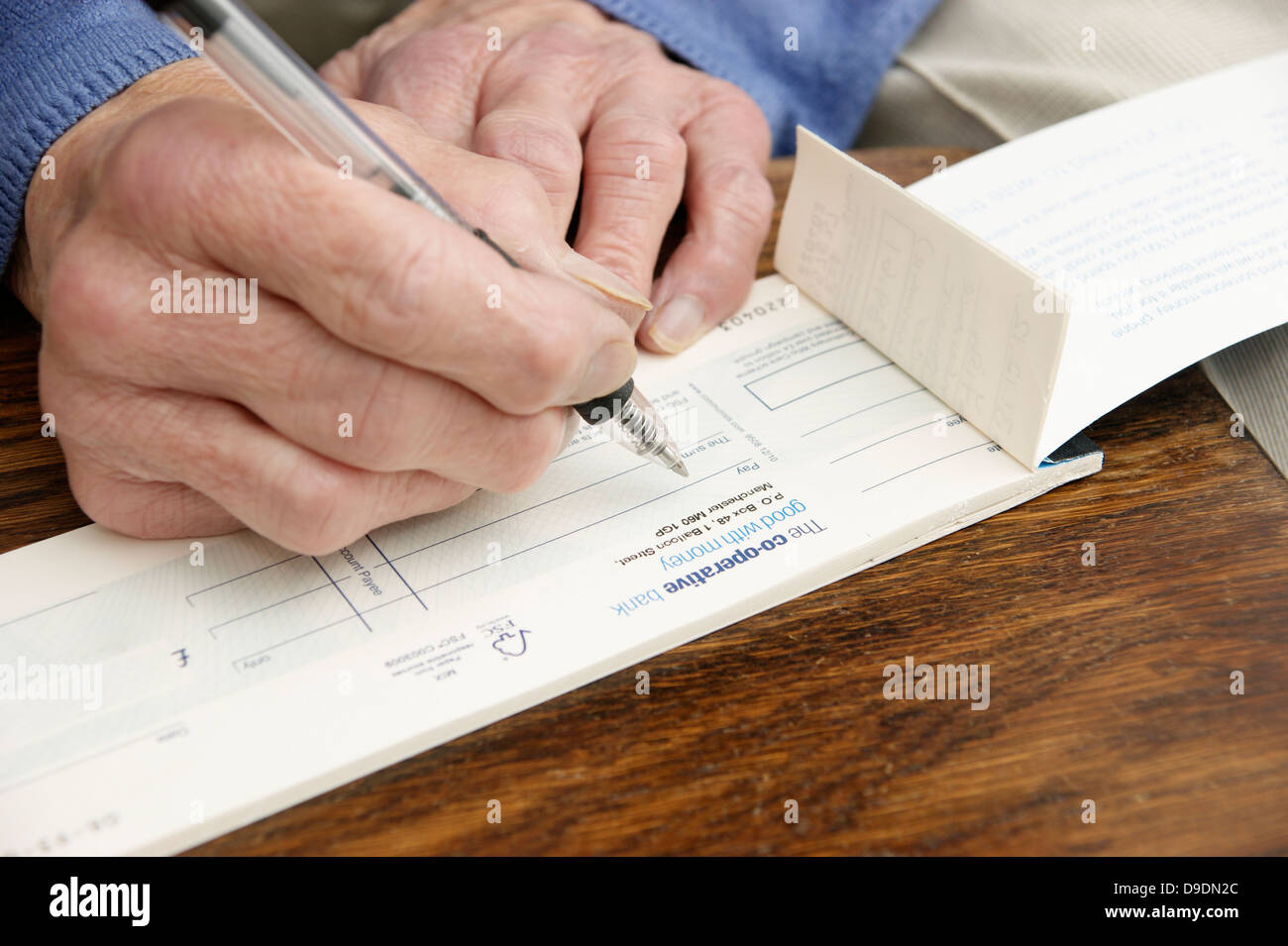 Elderly Woman Writing A Cheque Which Is Getting Rarer These Days  (cooperative Bank