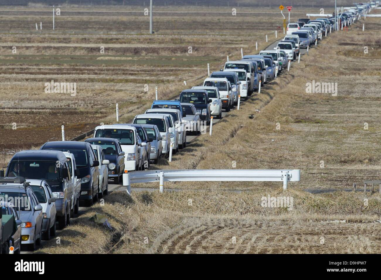 A very long line of cars snakes its way toward a gas station in ...