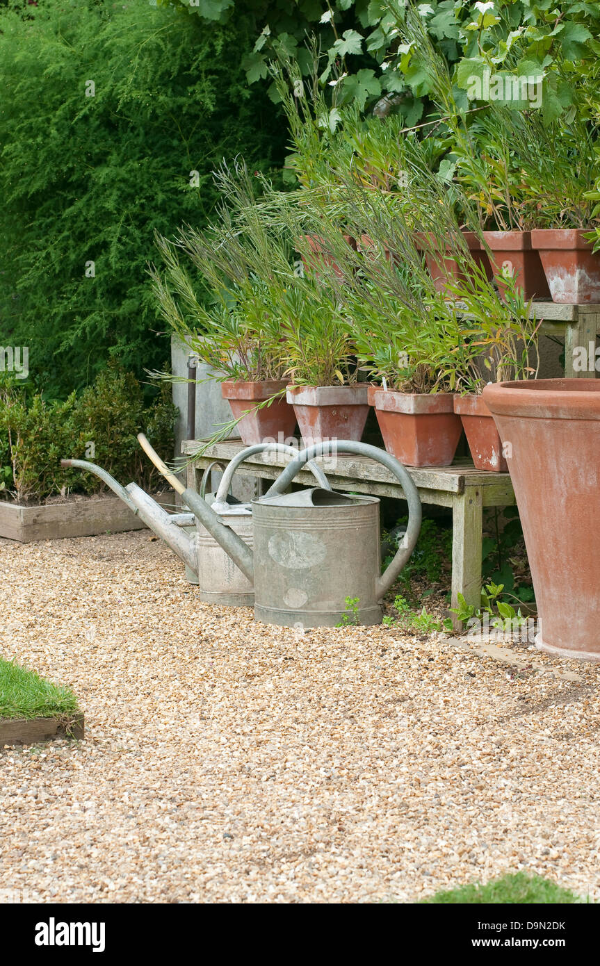 Watering Cans And Flower Pots In English Cottage Garden