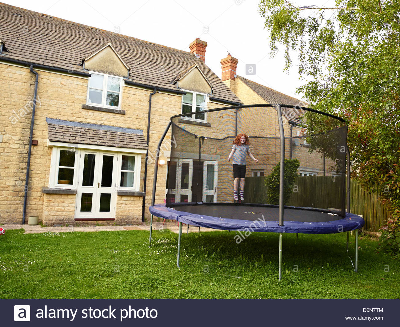 Young Girl Bouncing On A Garden Trampoline With A Safety Net At Dusk In The  Summer In Oxfordshire England UK