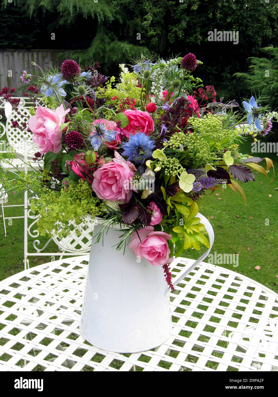 A Selection Of English Garden Flowers In A Simple White Vase In An English  Garden