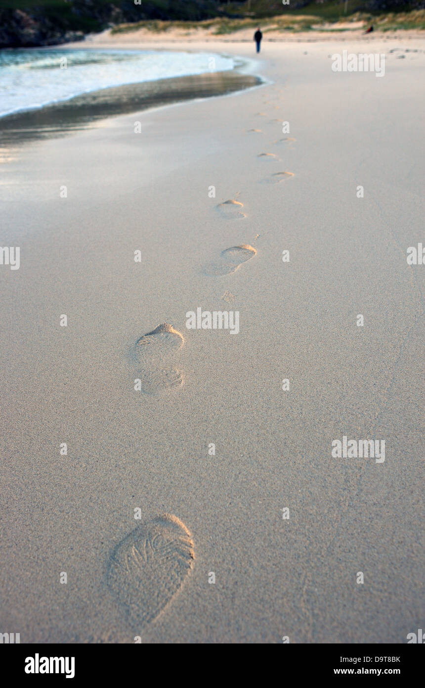 footsteps-on-a-beach-leading-to-a-man-in