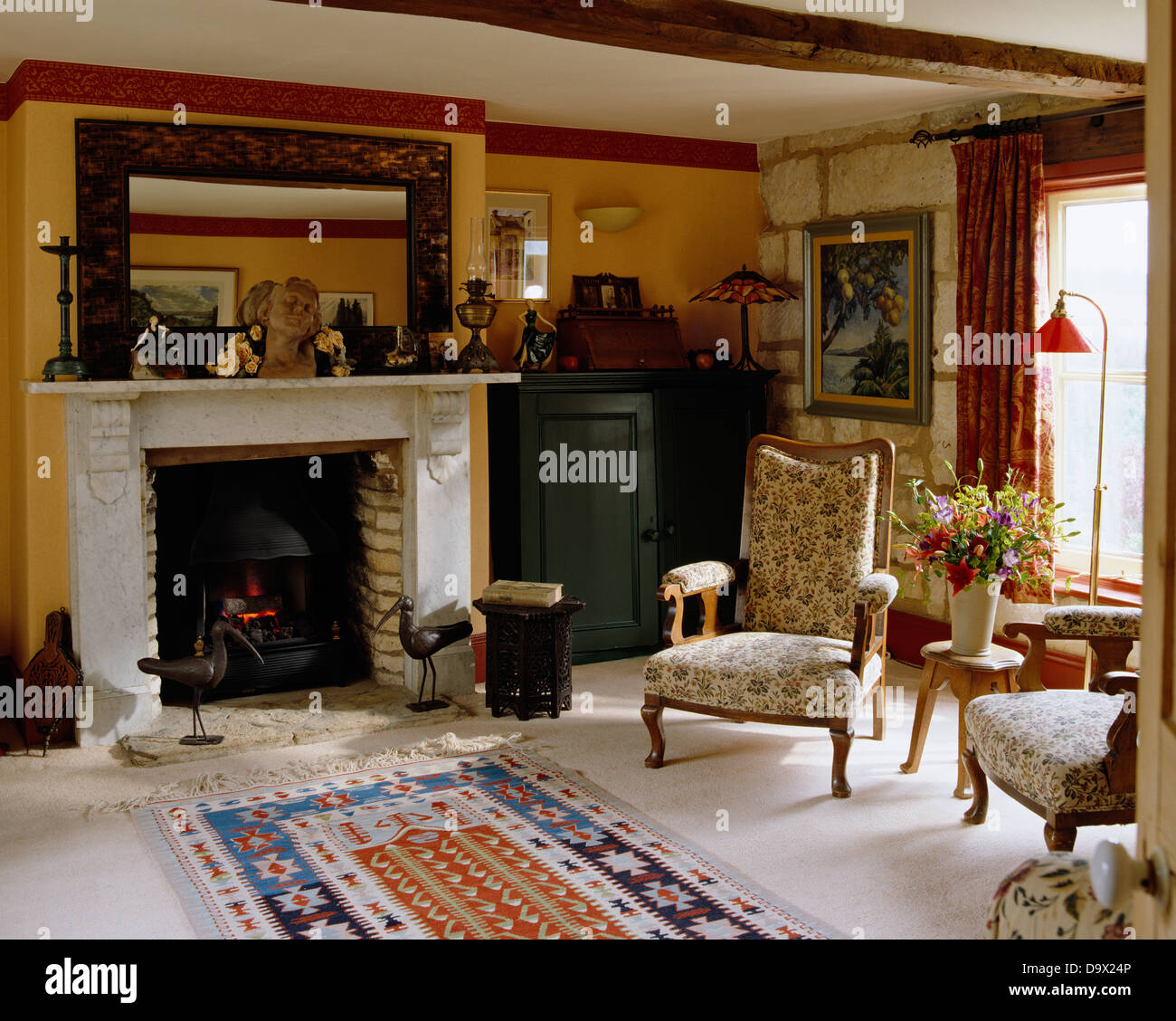 large mirror above fireplace with lit fire in yellow country
