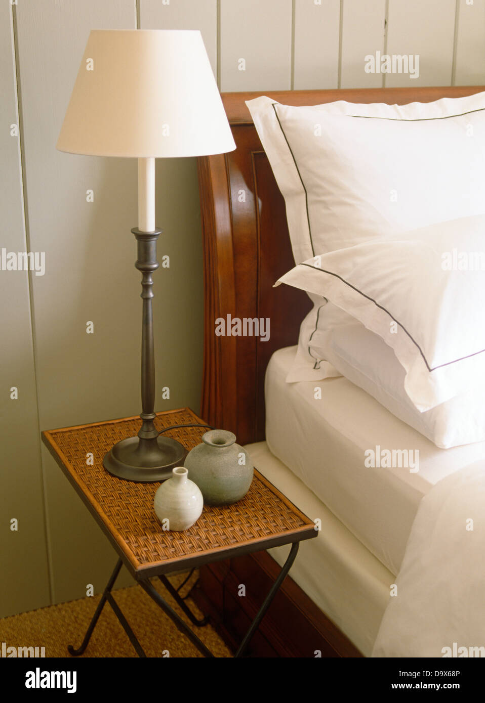 Lamp on wicker bedside table next to sleigh bed with crisp white pillows  and bed linen