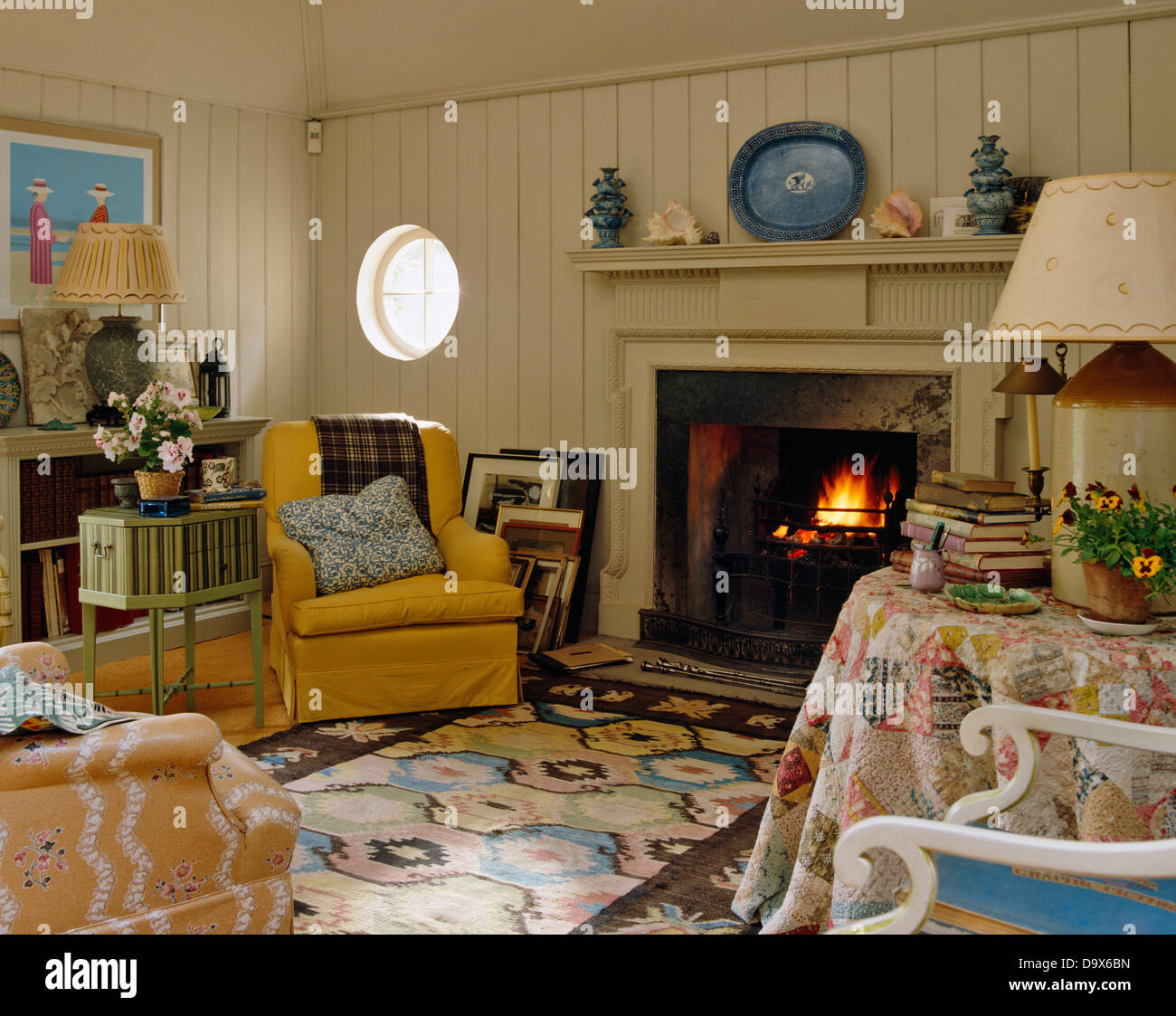 upholstered yellow armchair next to lit fire in country living