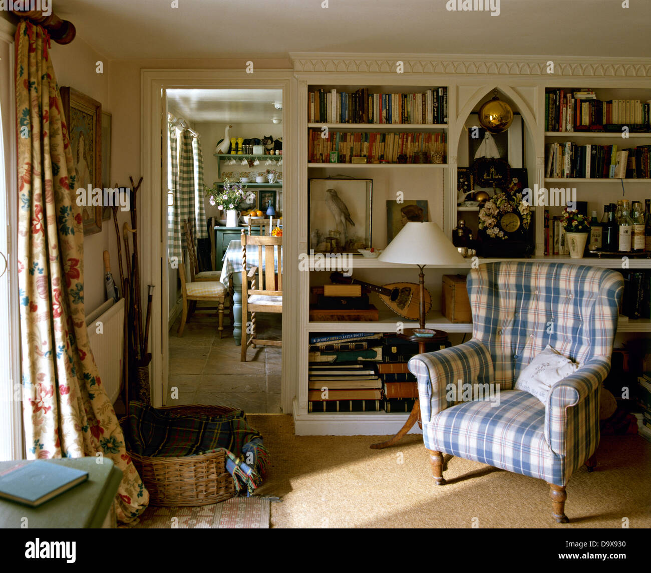 Cottage curtains - Blue Checked Upholstered Chair Beside Built In Bookcase In Cottage Sitting Room With Floral Curtains On The Window