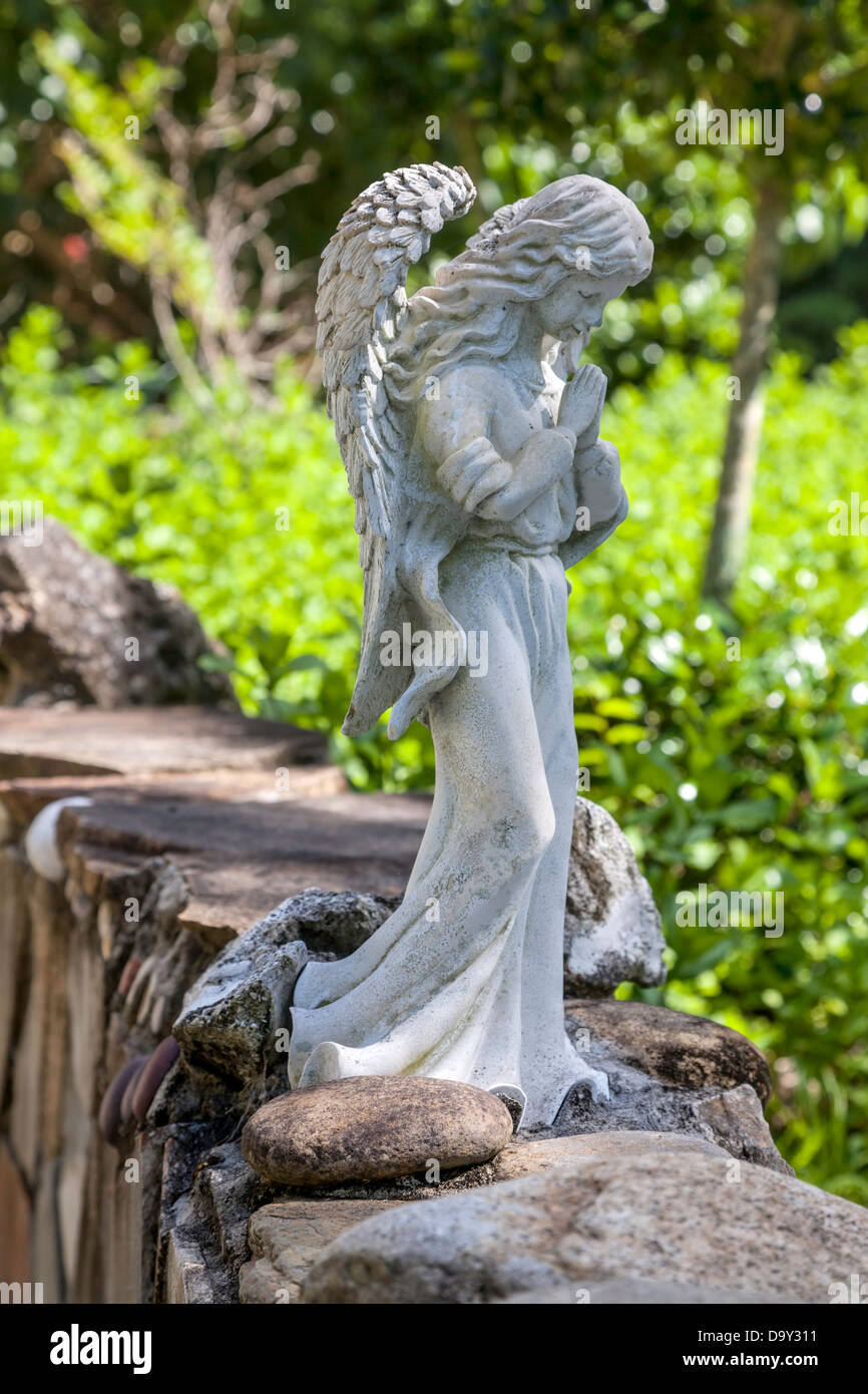 A Small Garden Statue Of A Pensive Or Praying Angel Sits Perched On A Low  Stone Garden Wall In Kanapaha Gardens.